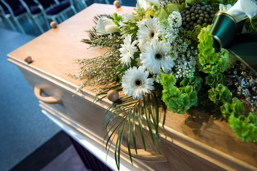 funeral coffin close up with flowers alternate angle